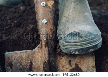Unrecognizable man digs by shovel land in garden, close-up - stock photo