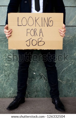 Unrecognizable man holding sign Looking for a job - stock photo