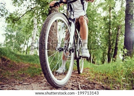 Unrecognizable man is riding bicycle on trail in summer park