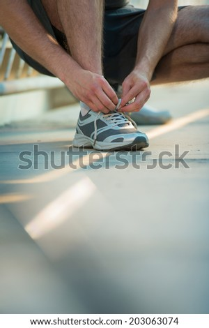 Unrecognizable man lacing his shoes before running outdoors