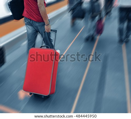 Unrecognizable man pulling trolley at train station.