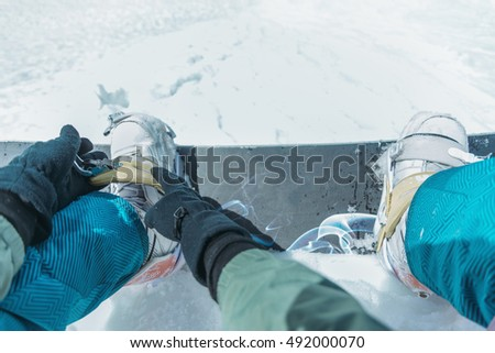 Unrecognizable man putting on his snowboard and tightening the straps on background of snow in winter, point of view