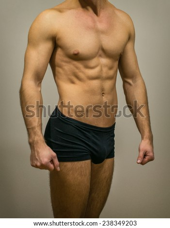 Unrecognizable muscular male body on grey background.