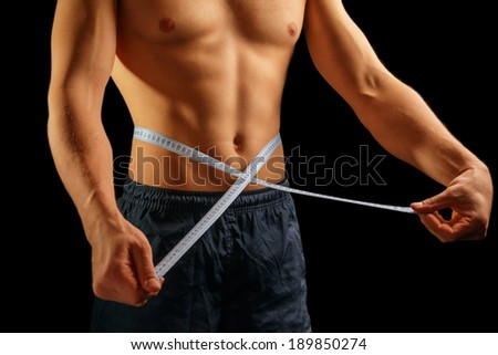 Unrecognizable muscular man is measuring waist with tape - stock photo