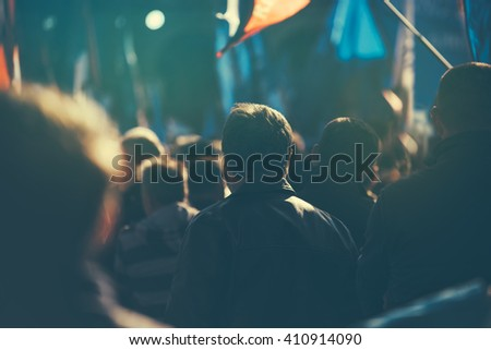 Unrecognizable people on the street during political meeting, audience from behind, selective focus and retro toned image with lens flare. - stock photo