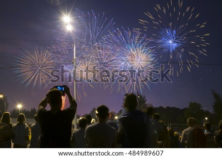 Unrecognizable people watch and shoot fireworks at night in Moscow, Russia, Festival in Brateevo