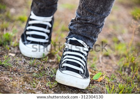 Unrecognizable person in rubber shoes walking on footpath, front view - stock photo