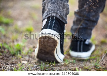 Unrecognizable person in running shoes walking on footpath, rear view