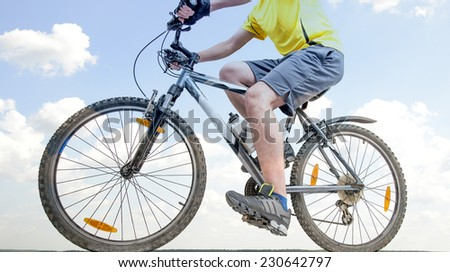 Unrecognizable person No face Mountain Biker on blue sky with clouds background Man wearing yellow sport shirt gray snickers and shorts Empty copy space for inscription