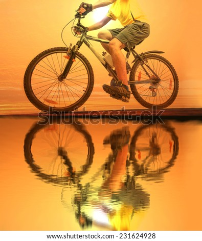 Unrecognizable person No face Mountain Biker on sky clouds background Man wearing yellow sport shirt gray snickers and shorts Empty copy space for inscription Reflection sun on yellow water texture  - stock photo