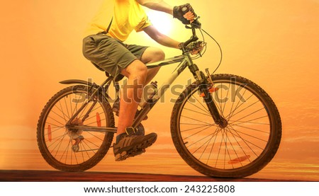 Unrecognizable person No face Mountain Biker on sky with background Man wearing yellow sport shirt sneakers shorts Empty copy space for inscription Reflection sun on yellow water texture  - stock photo