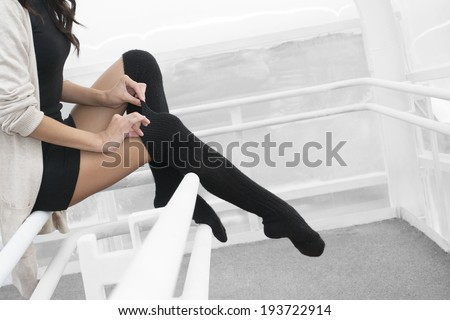 Unrecognizable person No face Woman legs in black pantyhose stockings indoor sits on metal railing Copy space for inscription Young adult girl wearing short dress, tightens thin fingers woolen tights - stock photo