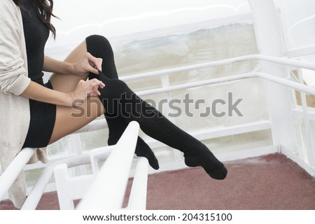 Unrecognizable person No face Woman legs in black pantyhose stockings indoor sits on metal railing Copy space for inscription Young adult girl wearing short dress tightens thin fingers woolen tights