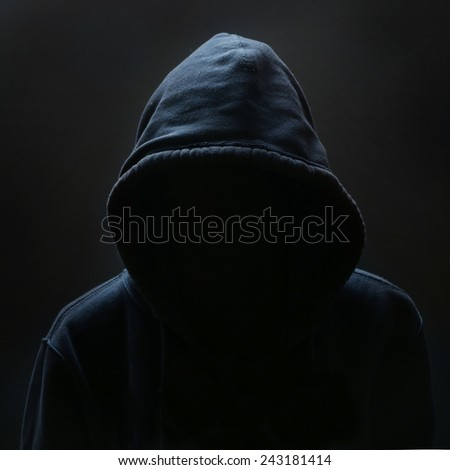 Unrecognizable person, Unrecognizable person wearing hood against black background  - stock photo