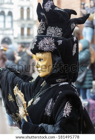 Unrecognizable persons wearing carnival costume (mask) in Saint Mark square in Venice, Italy. In 2014 the Carnevale di Venezia was held between 15 Feb - 04 Mar - stock photo
