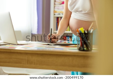 Unrecognizable pregnant woman in home office with laptop - stock photo