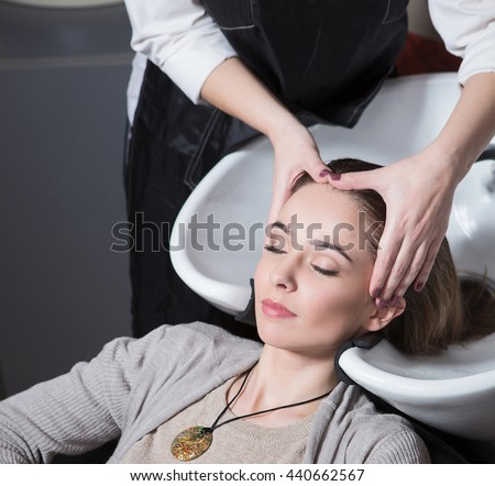 Unrecognizable professional hairdresser washing hair to her client. Beautiful hairdresser washing hair to her client lady in hairdressing saloon. Client sitting with her eyes closed.