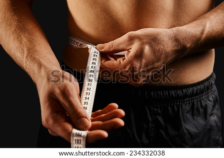 Unrecognizable sportsman measuring waist with centimeter tape - stock photo