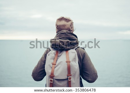 Unrecognizable traveler wearing in warm clothing with backpack enjoying view of sea, rear view - stock photo