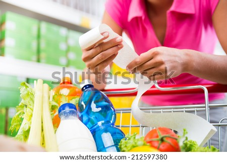 Unrecognizable woman checking a long grocery receipt leaning to a full shopping cart at store. - stock photo