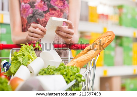 Unrecognizable woman checking a long supermarket receipt with grocery on foreground. - stock photo