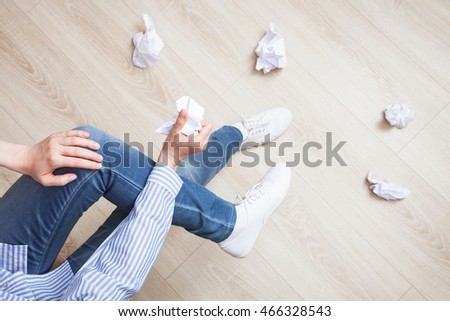 Unrecognizable woman crumpling paper and throwing it on the floor - upper viewpoint