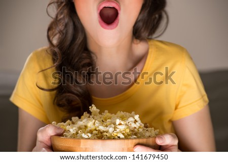 Unrecognizable woman eating popcorn at the cinema - stock photo