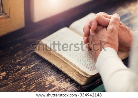 Unrecognizable woman holding a bible in her hands and praying - stock photo