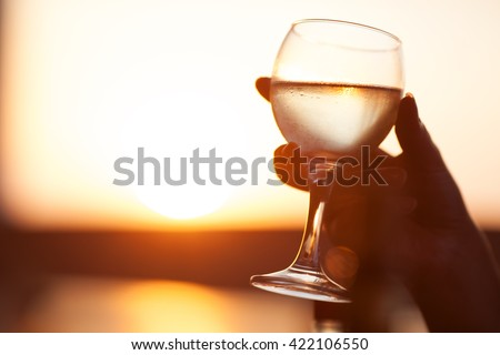 Unrecognizable woman holding glass of wine against of beautiful sunset