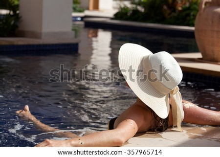 Unrecognizable woman in elegant hat relaxing on the luxury private swimming pool. Young tourist is enjoying summer vacation. - stock photo
