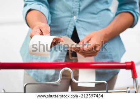 Unrecognizable woman in light blue shirt checking a long grocery receipt at store. - stock photo