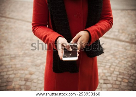 Unrecognizable woman in the street using her mobile phone, hands close up - stock photo