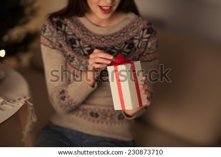 Unrecognizable woman opening Christmas gift at home - stock photo