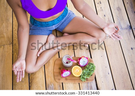 Unrecognizable woman sitting in lotus with fruits in front of her - stock photo