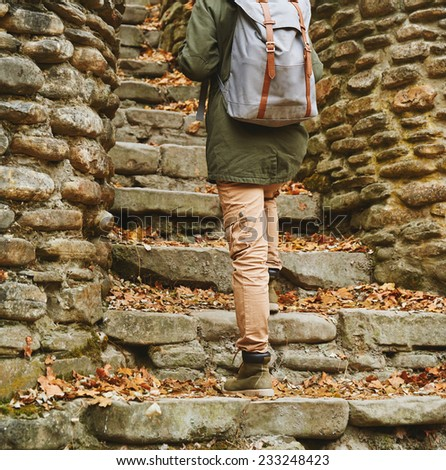 Unrecognizable woman with backpack walking up the old stone staircase in autumn outdoor, view of legs