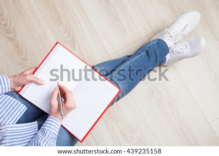 Unrecognizable woman writing in a red diary in a relaxed pose - upper point of view
