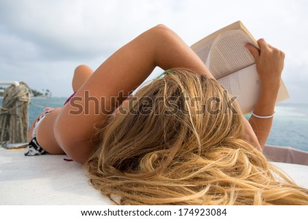 Unrecognizable young beautiful woman is relaxing and sunbathing while reading a book on a sailboat in the San Blas Islands, Panama 2014. - stock photo