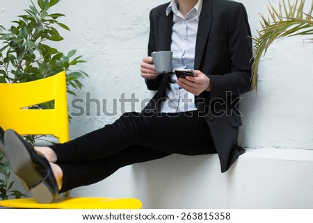 unrecognizable young business woman using her smartphone outdoors and relaxing.shallow depth of field with focus on the phone - stock photo