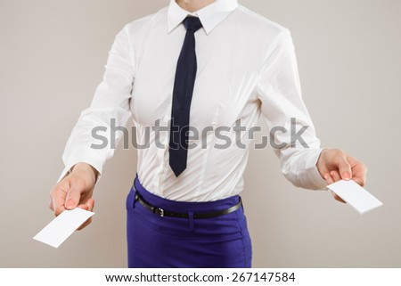 Unrecognizable young businesswoman dispensing business cards, neutral background - stock photo