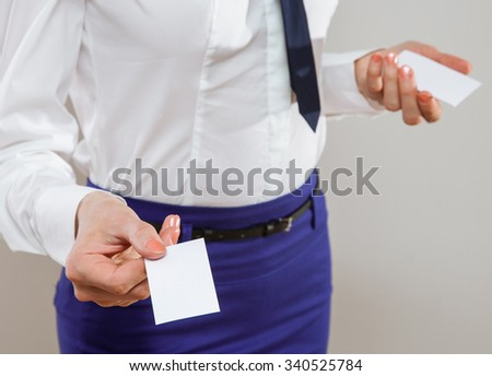 Unrecognizable young businesswoman dispensing business cards, neutral background