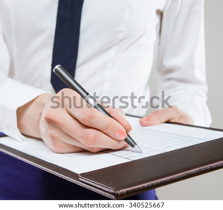 Unrecognizable young businesswoman  holding documents and a pen, neutral background
