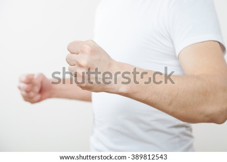 Unrecognizable young man prepared for fight, white background