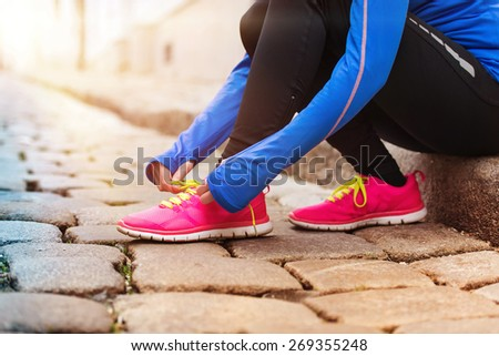 Unrecognizable young runner tying up her shoelaces - stock photo