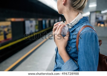 Unrecognizable young woman at the underground platform, waiting