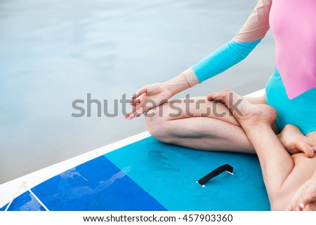 Unrecognizable young woman doing yoga on sup board with paddle. Meditative pose, front view - concept of harmony with the nature, free and healthy living, freelance, remote business. - stock photo