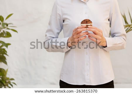 unrecognizable young woman holding a delicious muffin.shallow depth of field with focus on the hand - stock photo