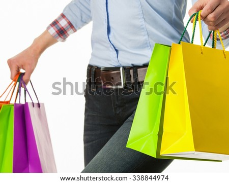 Unrecognizable young woman holding colorful paper bags, white background