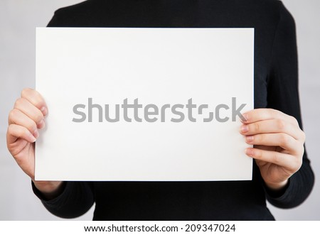 Unrecognizable young woman holding empty leaf of paper, neutral background