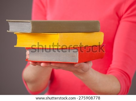 Unrecognizable young woman holding three books, gray background - stock photo
