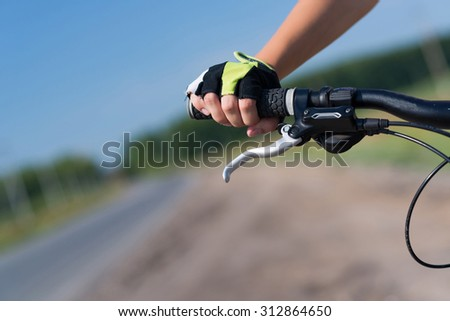 Unrecognizable young woman in shorts riding bicycle outdoors - stock photo